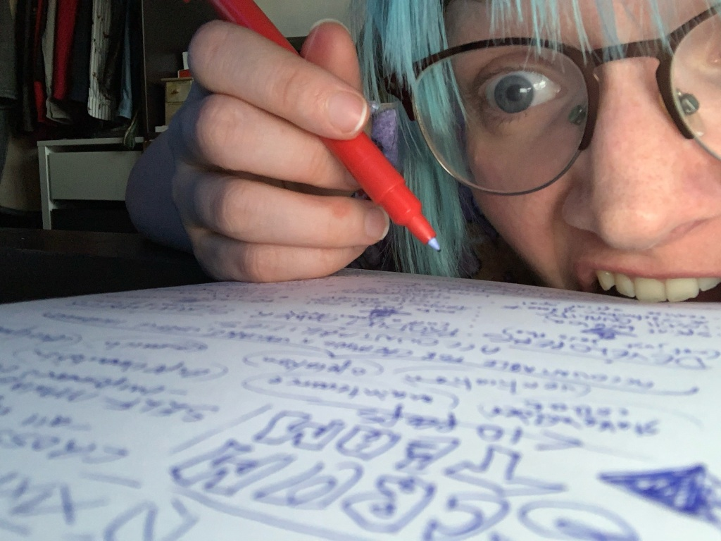 Photograph of me writing notes while biting the paper I am writing on in frustration.